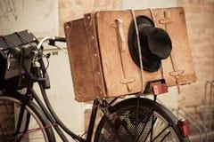 Chapeau noir et valise de Brown sur la vieille bicyclette Photos stock