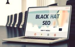 Chapeau noir SEO sur l'ordinateur portable dans la salle de conférence 3d Photographie stock