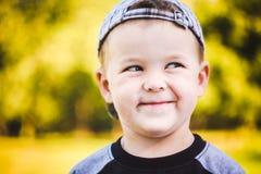 Chapeau rayé de port d'enfant heureux en portrait extérieur Photos stock