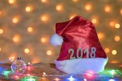 Chapeau rouge avec des chiffres de 2018 sur une table sur le fond d'un N Photographie stock