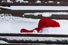 Chapeau rouge de Santa Claus sur le banc avec la neige Photo libre de droits