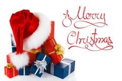 Chapeau rouge de Santa de Noël avec des cadeaux d'isolement sur le blanc Image stock