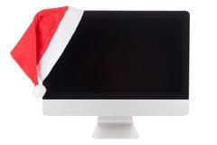 Chapeau rouge de Santa sur le moniteur moderne d'ordinateur photographie stock libre de droits
