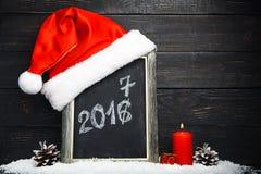 Chapeau rouge de Santa sur le tableau noir avec la neige Image stock