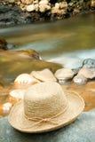 Chapeau sur des roches par le fleuve Photo stock