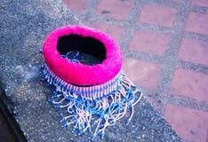 Chapeau tricoté de tissu, de bleu et de rose colorés Il a placé sur un banc en pierre C'est un chapeau pour l'enfant, fille penda Images libres de droits
