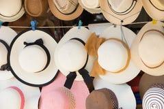 Chapeaux de paille à vendre, accrochant sur un mur photographie stock