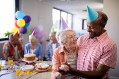 Chapeaux de port de partie de couples supérieurs heureux avec des amis Image stock
