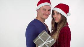 Chapeaux de port de Noël de jeunes couples affectueux souriant à la caméra, tenant un cadeau banque de vidéos