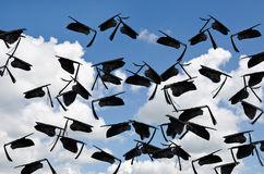 Chapeaux noirs d'obtention du diplôme en ciel Photographie stock