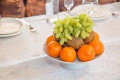 Chapeie com as laranjas, as uvas, o quivi com vidros vazios e o faqueiro dos frutos no fundo Fotografia de Stock Royalty Free