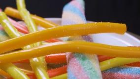 Chapeie completamente do doce de fruta colorido que está sendo arrebatado acima por três meninas com fome das crianças Perto acim filme