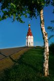 Chapel. Church, temple, road, tree, birch, sky, blue, summer, green, red, roof stock photography