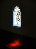 In the Chapel. A beam of sunlight shines on a church pew in a small chapel stock photos