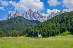 Chapel in the Alps. Chapel in a green field with mountains in the background royalty free stock images