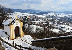 Chapel of Banska Stiavnica calvary near  upper church during winter season with snowy stairway and part of cityscape in background. Winter 2018 Royalty Free Stock Photography
