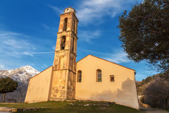 Chapel and bell tower near Pioggiola in Corsica. Old chapel and bell tower near Pioggiola in the Balagne region of Corsica with a snow capped San Parteo in the Stock Photography
