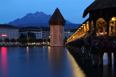 Chapel Bridge In Lucerne At Dusk. The famous Chapel Bridge / Kapellbrücke in Lucerne, Switzerland. Mount Pilatus is visible in the background stock image