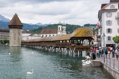 Chapel Bridge, Lucerne. Lucerne, Switzerland June 9 2013: Beautiful Chapel Bridge and tower with many tourists around, swans in the water and mountains in the Stock Image