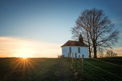 Chapel on the hill at sunset, with sun rays. Chapel on the hill beside a tree, at sunset with sun rays over the hill. peaceful meditation place bavaria stock photography