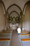 Chapel interior. Inside a small chapel with a single worshipper sitting on a bench Royalty Free Stock Image