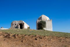 Chapel / mosque on a hill, Morocco. Chapel / mosque of a hill, out of any city or village. Building with older white facade and with dome. Bright blue sky stock images