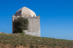 Chapel / mosque on a hill, Morocco. Chapel / mosque of a hill, out of any city or village. Building with older white facade and with dome. Bright blue sky stock image