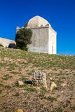 Chapel / mosque on a hill, Morocco. Chapel / mosque of a hill, out of any city or village. Building with older white facade and with dome. Bright blue sky royalty free stock photo
