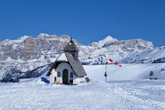 Chapel in the moutains. White chapel on the hill in snowy mountains Royalty Free Stock Photography