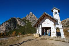 Chapel with Sass de Stria mountain in background on Falzarego Pass Passo di Falzarego at sunny autumn day. Dolomites Alps, Italy royalty free stock images