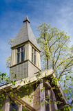 Chapel Steeple in Springtime. A green and gray chapel steeple sits calmly in front of a budding tree in spring stock photos