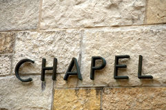 Chapel text on stone-angle. Sign spelling 'Chapel' in metal letters on limestone brick wall in neutral tones shot straight at an angle. Letters are set in front Royalty Free Stock Photo