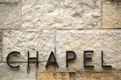 Chapel text on stone. Sign spelling 'Chapel' in metal letters on limestone brick wall in neutral tones shot straight on.  Letters are set in front of wall and Stock Photography