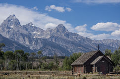 Chapel of the Transfiguration and mountains. Chapel of the Transfiguration, a small church in front of the Cathedral Group, some of the tallest mountains in Royalty Free Stock Image
