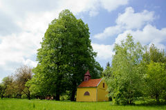 Chapel Under The Big Lime-Tree. And Blue Sky with White Clouds Royalty Free Stock Photos