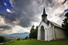Chapel under stormy skies. Wide-angle image of a little chapel, on a hillside in France, under wild cloudy skies. The sun behind the chapel.  Mountains in the Stock Image