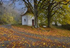 Chapel on the village green. In foggy November morning Royalty Free Stock Photo