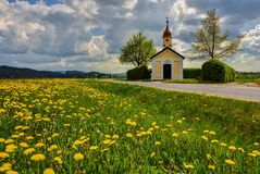 Chapel of the village. Picturesque chapel on the road in the spring afternoon Stock Photography