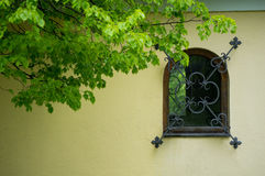 Chapel window. And iron decorative grill and bright green leaves Royalty Free Stock Images