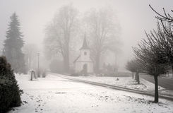 Chapel in winter mist. In the village Royalty Free Stock Photo