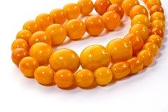 Chapelet ambre se trouvant sur une surface blanche Image stock