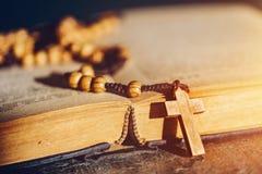 Chapelet avec la croix s'étendant sur un livre de bible image stock