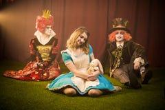 Chapelier et Alice heureuse et la reine alarmée image stock