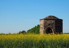 Chapelle abandonnée antique dans la campagne, devant un gisement de canola Image stock