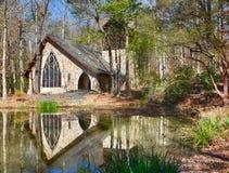 Chapelle en pierre avec le vitrail de tache se reflétant dans l'eau du lac de lac photographie stock libre de droits