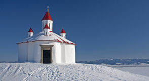 Chapelle sur la colline neigeuse Photographie stock libre de droits