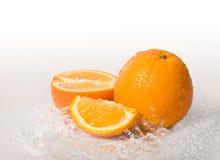 Chapoteo anaranjado de la fruta y del agua Fotos de archivo libres de regalías