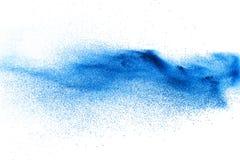 Chapoteo azul de las párticulas de polvo del color en el fondo blanco Fotografía de archivo