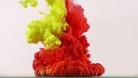 Chapoteo colorido de los descensos de la tinta de la pintura en submarino en piscina de agua