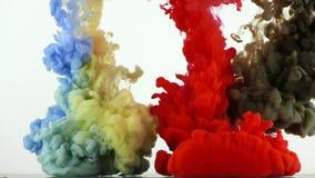 Chapoteo colorido de los descensos de la tinta de la pintura en submarino en piscina de agua almacen de metraje de vídeo